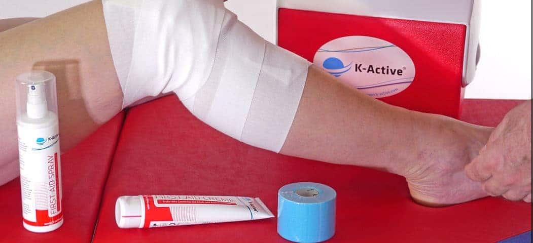 Knie mit Tapeverband und medizinischen Produkten