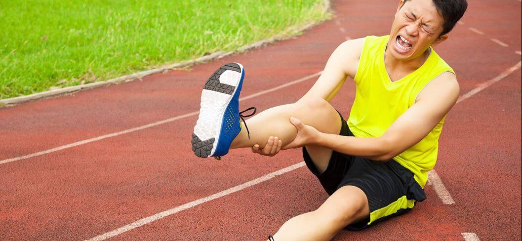 Sportler mit schmerzverzerrtem Gesicht sitzt auf Boden und hält seine Wade