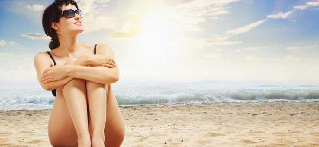 Frau mit Sonnenbrille sitzt am Sandstrand und schaut in die Sonne